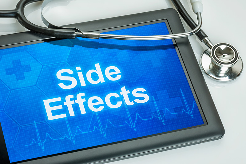 "tablet with ""side effects"" shown on the screen and a stethoscope lying next to it"