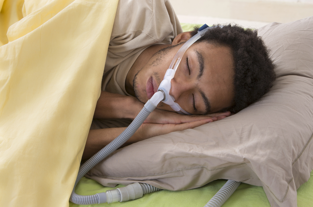 African American man sleeping with a CPAP machine