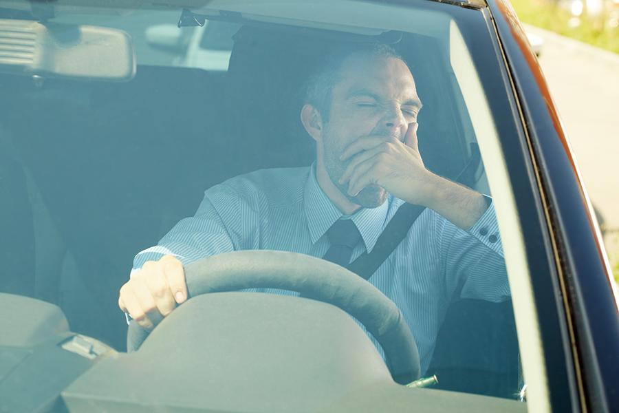 Tired man yawning in his car