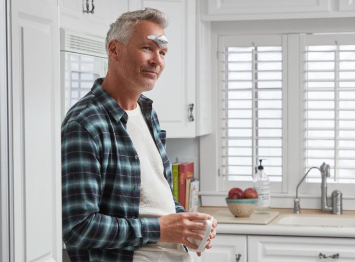Homme à la maison dans sa cuisine à l'aide de son appareil Cefaly pour prévenir et traiter ses migraines