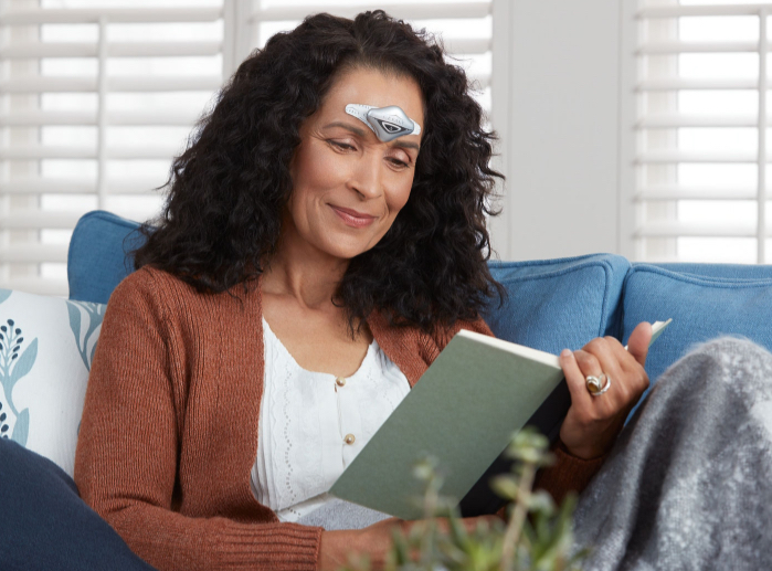 Woman reading a book while using her Cefaly device to prevent and treat her migraines