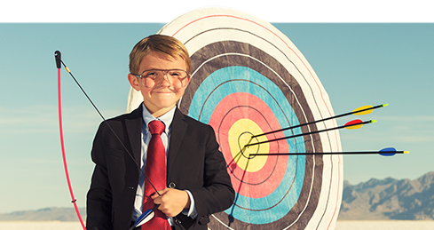 boy in suit with bow and arrow in front of a target