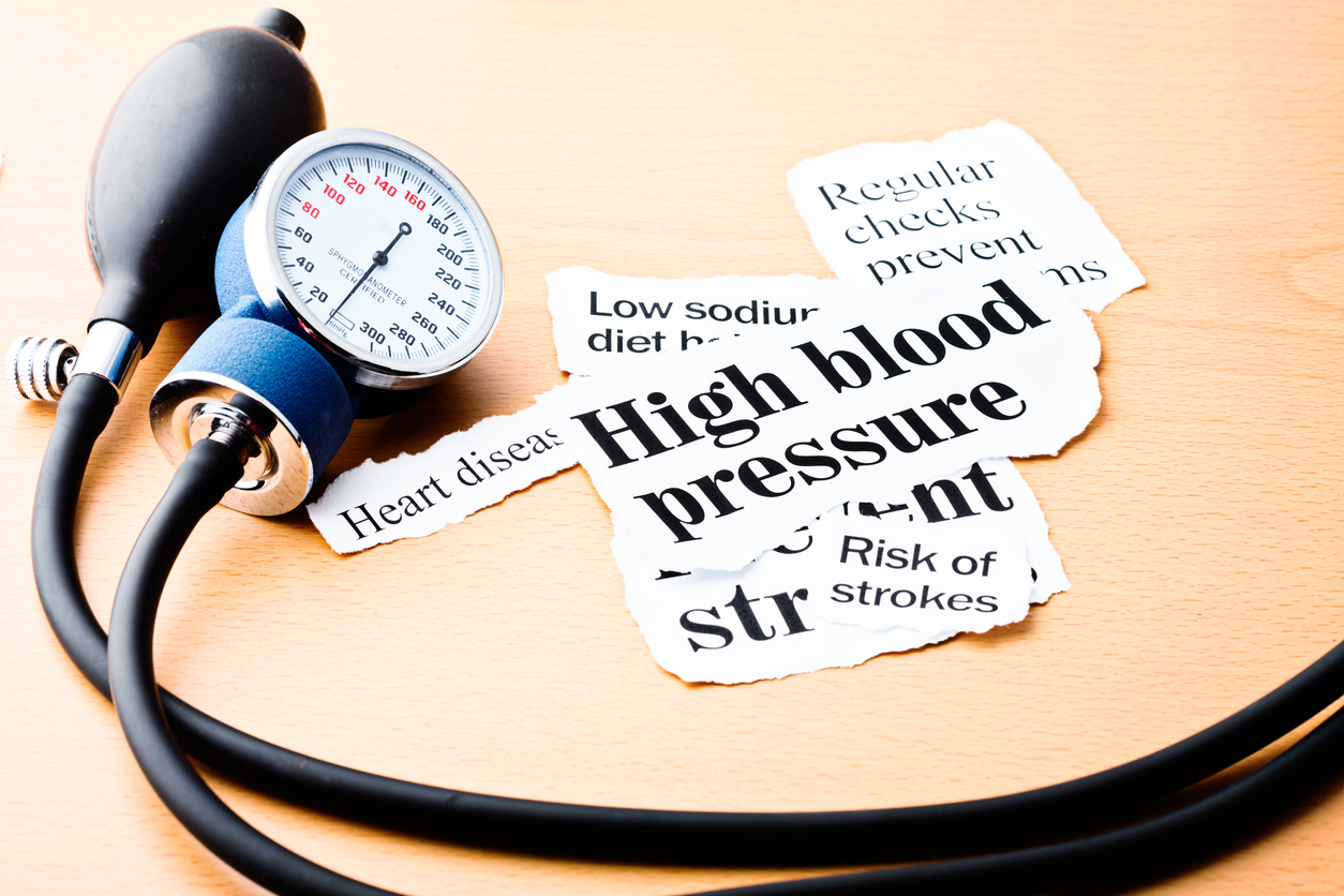 Headlines on high blood pressure, heart disease, and the risk of strokes on a wooden desk next to a blood-pressure gauge.
