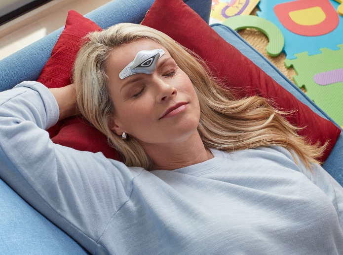Woman laying down with her eyes closed using her Cefaly device to prevent and treat her migraines