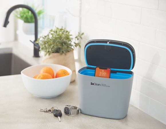 Image of Soclean Device on Countertop next to a fruit bowl with oranges in it.  Next to the unit infront there is a watch and some keys.  The Soclean device is gray, opens at the top and has a blue interior.  In this particular pucture there is also a phone inside it.  The unit is open, resumably ready for disinfection procedure.  The background is a white kitchen backslpash, further back there is a farm style sink under a finely beveled granite countertop the color of beige or sand.  In the picture it is proabbly about noon time.
