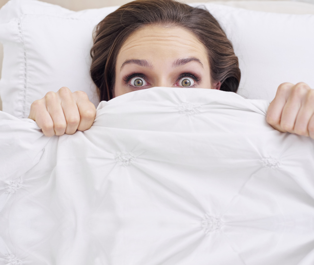 A young woman peeking out from under her bed sheet with a frightened expression.