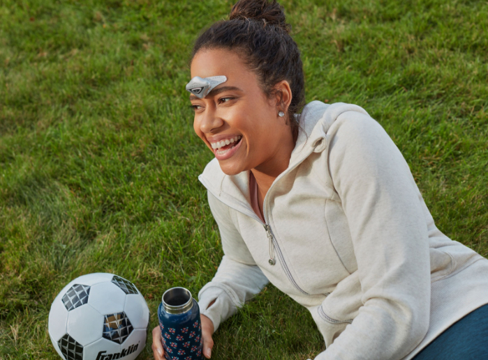 Woman laying in the grass at a sporting event wearing a Cefaly Migraine treatment and prevention device on her forehead