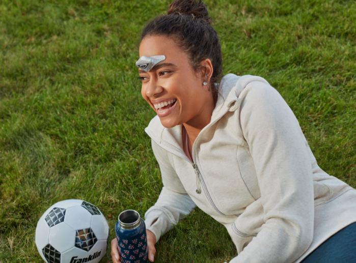Femme allongée dans l'herbe lors d'un événement sportif portant un dispositif de traitement et de prévention de la migraine Cefaly sur son front