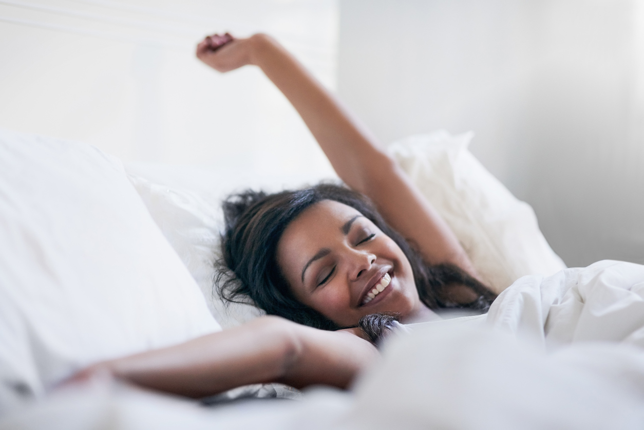 Shot of a happy young woman waking up in her bed at home