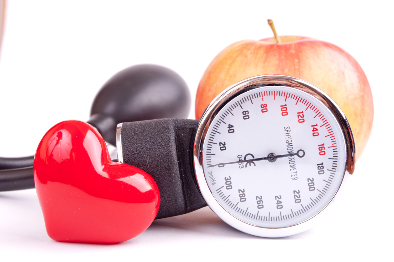 Blood pressure gauge, apple and heart isolated on white background