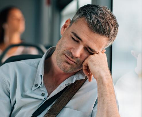 tired man sleeping in public