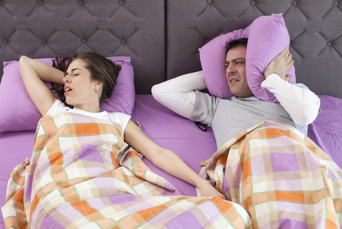 disgruntled husband glaring at snoring wife in bed