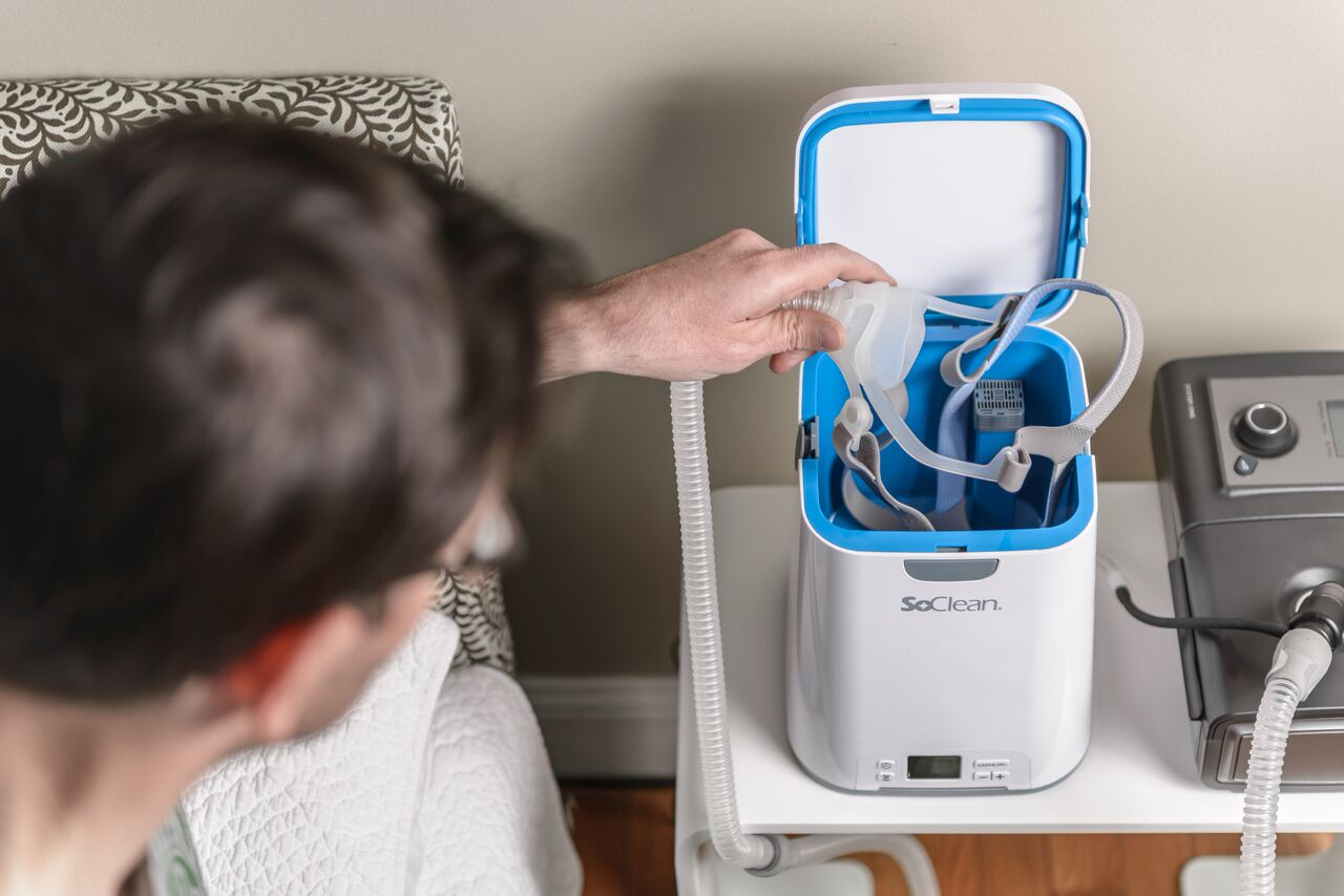 Man placing CPAP mask into SoClean 2