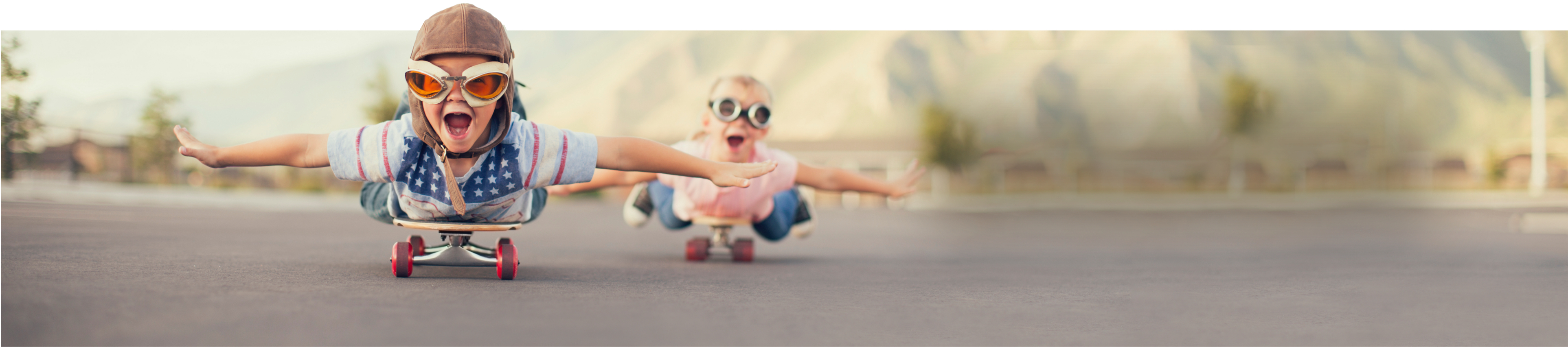 Two kids laying on skateboards pretending to fly