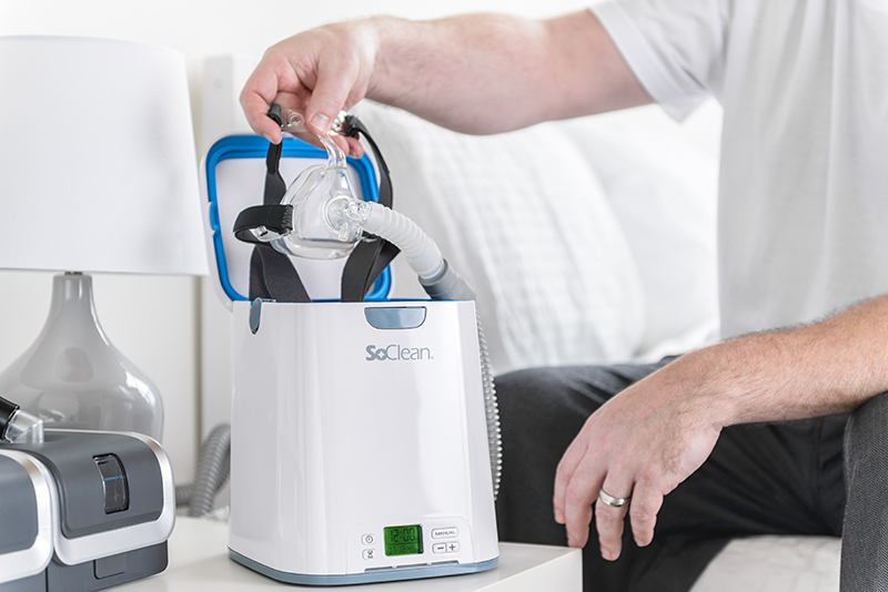 Man placing CPAP mask in SoClean 2.
