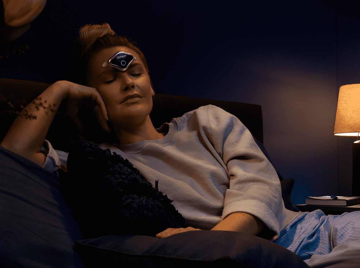 Woman using Cefaly DUAL while relaxing