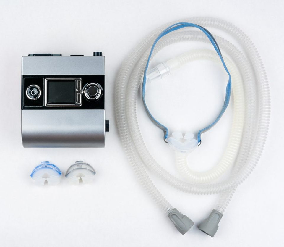 CPAP machine with hose and nasal mask.