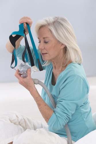 elderly woman putting onm a CPAP mask