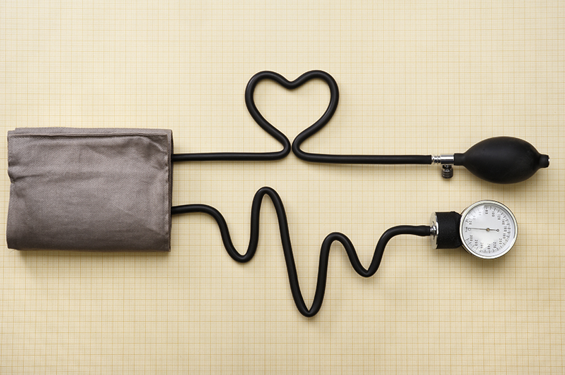 A bloog pressure sleeve with its cords in the shape of a heart and an EKG.